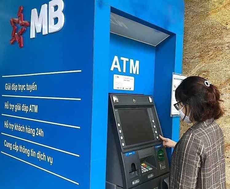 Khách hàng đang tra cứu số tài khoản ngân hàng MB Bank tại cây ATM